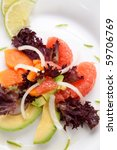 Closeup of papaya, avocado and grapefruit salad with sweet onion and lime wedges - stock photo