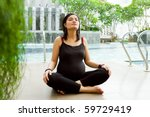 Asian ethnic pregnant woman doing breathing exercise by the pool - stock photo