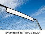 sign fixed to metal fencing with blank copy area - stock photo