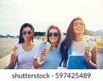 three joyful young girlfriends... | Shutterstock . vector #597425489