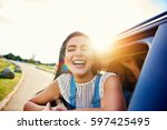 Small photo of Pretty woman in speeding car smiles at camera while friends laugh in seat behind her