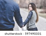 young couple holding hands  ... | Shutterstock . vector #597490331