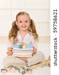 Happy girl with books and alphabet wooden blocks - back to school theme - stock photo