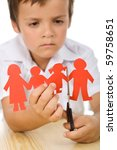 Sad kid cutting his paper people family - divorce concept, closeup - stock photo