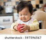baby girl eating apple | Shutterstock . vector #597596567