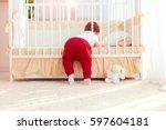 cute toddler baby climbing into ... | Shutterstock . vector #597604181
