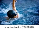 Professional male swimmer in a pool with hat and goggles - stock photo