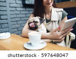 Stock photo adorable pug dog sitting in his owner s lap in cafe bar selective focus on dog 597648047