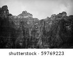 Small photo of The headwall of the cirque that looms over Iceberg Lake. The cliffs on the mountains form a perfect ampitheater around the lake. Shadows from clouds provide contrast. In black and white.