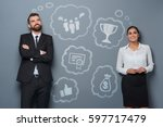 Small photo of The business goals. Two ambitious business beginners ponder their wishes and aspirations depicted in clouds. People in formal clothing in front of a gray wall and illustration painted with chalk.