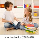 Let me tell you about school - siblings with books talking at home, back to school concept - stock photo