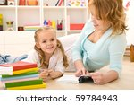 Woman reading to her little girl laying on the floor in the kids room - stock photo