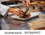 chef in restaurant arrangin and ... | Shutterstock . vector #597869957
