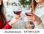 Small photo of Two female friends drinking wine in restaurant