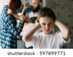 sad child covering his ears... | Shutterstock . vector #597899771