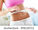slim young woman measuring her... | Shutterstock . vector #598120721