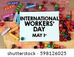 Small photo of A happiness concept image of a colorful beads and cute clothespin scattered over a colorful wooden texture background with a white canvas and a word celebrate INTERNATIONAL WORKERS DAY - MAY 1