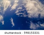 Small photo of Beautiful altocumulus and cirrocumulus white clouds against blue contrast saturated evening sky