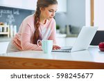 young woman sits at the kitchen ... | Shutterstock . vector #598245677