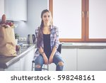 young woman sitting near table... | Shutterstock . vector #598248161