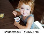 cute little boy eating yogurt.  | Shutterstock . vector #598327781