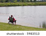 Lonely Young Man Fishing by the Pond - stock photo