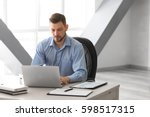 Small photo of Handsome manager working with laptop in office