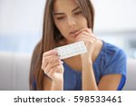 young woman with pills at home  ... | Shutterstock . vector #598533461