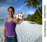 Young Woman On The Beach Holding A Shell In Her Hand With Sale Written On It! - stock photo