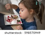 little cute girl in cafe eats a ... | Shutterstock . vector #598570949