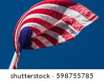 an american flag curls in... | Shutterstock . vector #598755785
