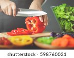 female cutting red bell peppers....   Shutterstock . vector #598760021
