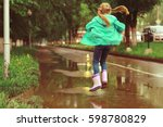 girl jumping in the puddles in... | Shutterstock . vector #598780829