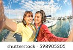 Young women girlfriends taking selfie at sailboat dock - Friendship concept with happy rich girls having fun together - Best female friends enjoying moment with mobile smart phone - Warm vivid filter