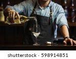 male sommelier pouring white... | Shutterstock . vector #598914851
