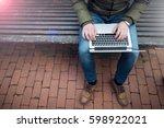 laptop in a man's hands sitting ... | Shutterstock . vector #598922021