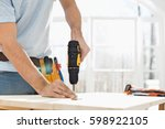 midsection of man drilling nail ... | Shutterstock . vector #598922105