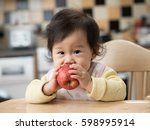 baby girl eating apple | Shutterstock . vector #598995914