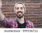 young latin man taking a selfie.... | Shutterstock . vector #599156711