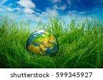 globe lies on green grass.... | Shutterstock . vector #599345927