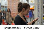 woman buys chocolate in a... | Shutterstock . vector #599353589