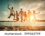 friends jumping on the beach... | Shutterstock . vector #599363759