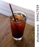 Small photo of Americano with ice on table wood with blur background