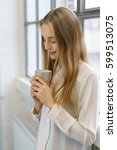 Small photo of Young woman enjoying a quiet mug of coffee holding it in her hands savoring the aroma as she stands in front of a window