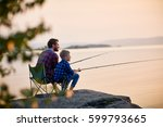 Small photo of Side view portrait of father and son sitting together on rocks fishing with rods in calm lake waters with landscape of setting sun, both wearing checkered shirts, shot from behind tree