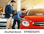 young couple choosing new car... | Shutterstock . vector #599805695