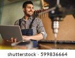 carpenter works on the computer ... | Shutterstock . vector #599836664