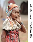 Small photo of Luang Namtha prov., Laos-October 6, 2015: The Akha hill tribe are an ethnic minority living in the mountains between E.Myanmar-N.Thailand-W.Laos-S.China. Old woman greets tourists visiting the village