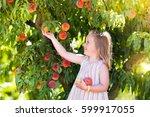 little girl picking and eating... | Shutterstock . vector #599917055