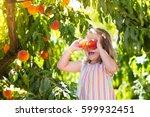 little girl picking and eating... | Shutterstock . vector #599932451